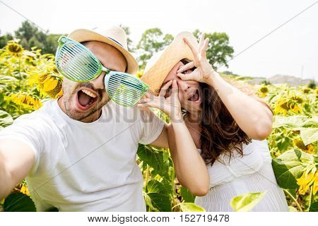young happy couple man and woman are in a field of sunflowers make selfie pics grimace and fun