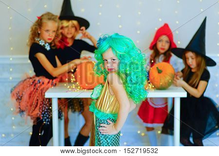 Happy group of children in costumes during Halloween party playing around the table with pumpkins and bottle of potion