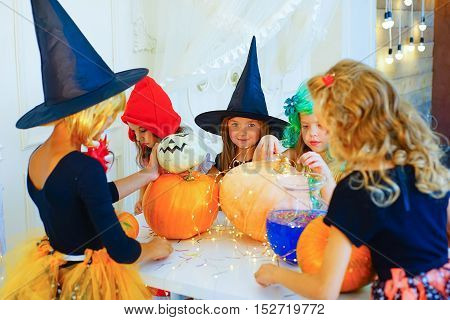 Happy group of children in costumes preparing for Halloween playing around the table with pumpkins and bottle of potion