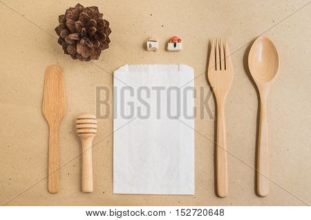 Top view of white paper bag spoon fork butter knife and honey dipper on brown background