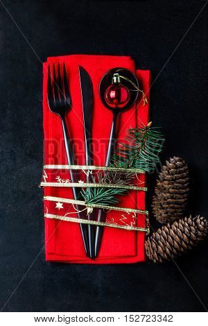 Christmas New Year background. Christmas menu background with copy space. Black steel cutlery set fork, knife, spoon on red napkin with decoration Holiday gold ribbon, Christmas red ball. Top view