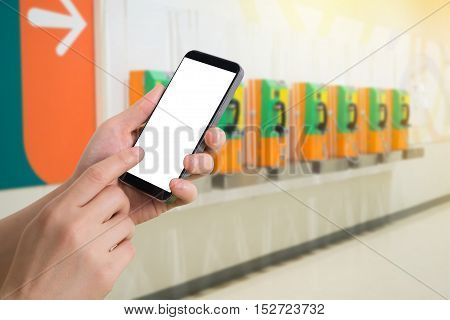 human hand hold and touch smartphone tablet cell phone with blank screen on blurry obsolete phone booth concept of change in communication.