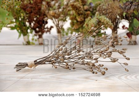 Dry grass bound in a bundle on a wooden surface closeup.