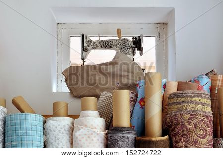 Antique sewing machine standing on a small window. Ravels of different tissues in the foreground.