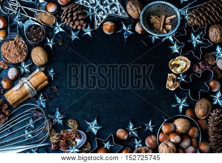 Christmas New Year Holiday baking background with ingredients, spices, nuts, cookie cutters, fir tree cones and christmas decoration