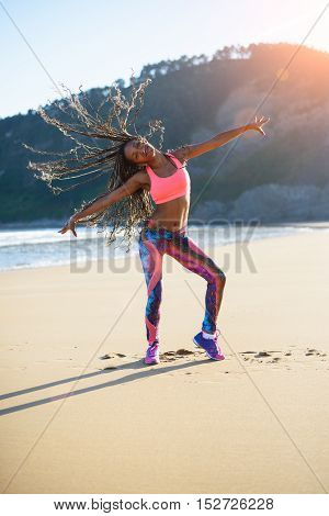 Sporty woman with long hair braids dancing and having fun at the beach on summer sunset. Black happy dancer training outdoor.