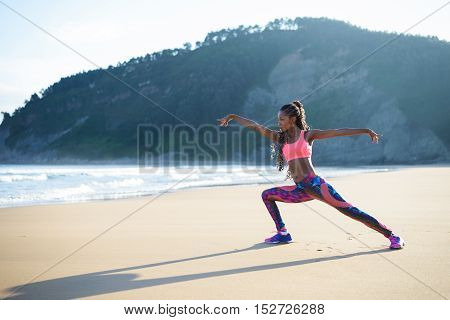 Fitness woman stretching legs and practicing dancing poses at the beach. Black female athlete working out outdoor against the sea.