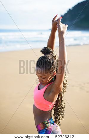 Black beautiful sportswoman stretching and training at the beach on summer. Fitness outdoor workout.