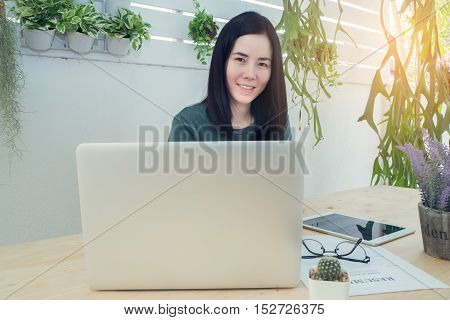 Office table with laptop and blank screen on laptop Asian woman smile face. wood table with office equipment and lavender flower on pot at tree garden. View from front office table.