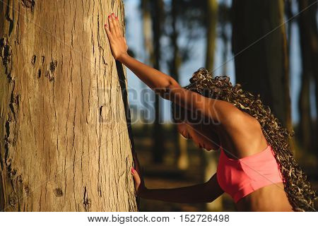 Fitness black woman training in nature. Outdoor workout and healthy activity. Female athlete stretching pushing against a tree.