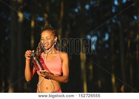 Cheerful sporty brazilian woman taking a fitness workout rest for drinking water and listening music. Black female athlete wearing earphones.
