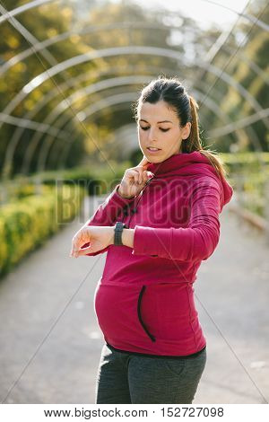 Pregnant fitness woman measuring heart rate and resting during outdoor workout. Tired gravid female taking a training rest. Pregnancy healthy lifestyle and exercise.