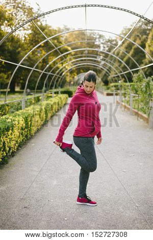 Fitness pregnant woman stretching legs and exercising outdoor at urban park on early autumn. Gravid female athlete training outside.