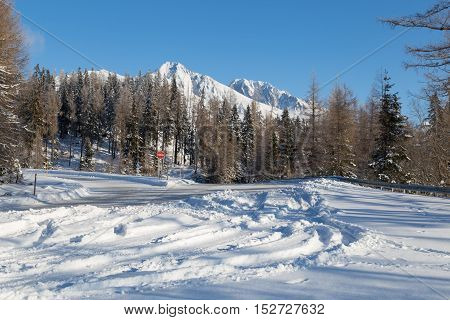 Winter snow covered road with view of snowy peaks mountains against the blue sky. Turning to the famous ski resort of Strbske Pleso. High Tatras. Slovakia.