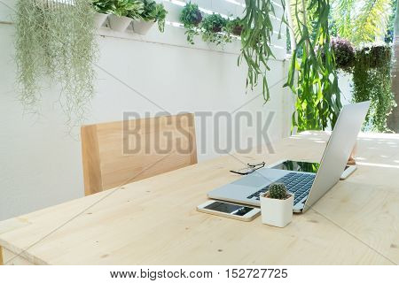 office table and wood chair with notebook tablet coffee cup and cactus flower on pot at tree garden background Natural office for working at home Tree garden with office table Work place at home.