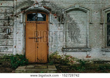 orange wooden door of an old abandoned building