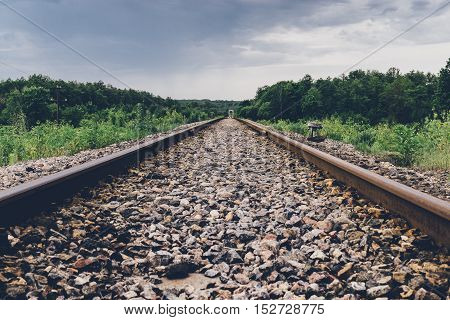 railway tracks in the woods  and dark clouds sky