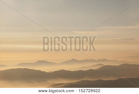 Cloudscape shot during golden hour with mountains in background
