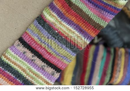Striped colorful woolen knitted fabric closeup on brown cardboard. Blurred background.
