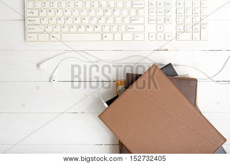 top view of earphone with computer keyboard with stack of book on white wood background