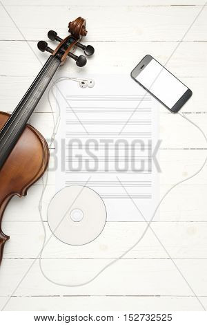 violin with music paper note dvd disc and smart phone on white wood background