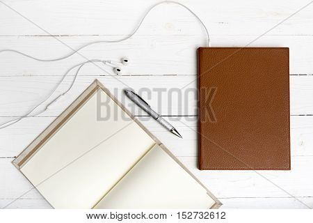 top view of notebook and earphone on white wood background