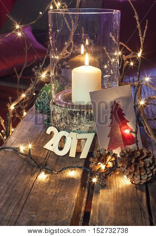 Happy new year 2017 christmas decoration big candle with tree lights and numbers on wooden surface vintage warm colors variation