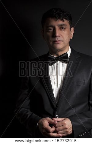 Elegant man wearing black bow tie and black suit on black background