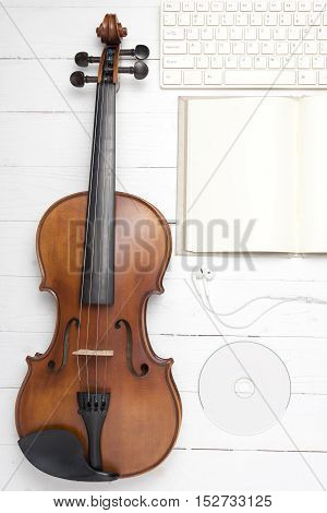 keyboard computer notebook dvd disc and violin on white wood background