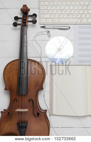 keyboard computer with notebook dvd disc and violin on white background