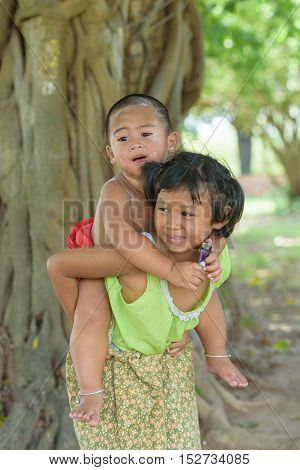 little asian boy sit on young girl's back they dress in Thai local dress and play outdoor together.