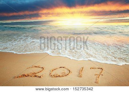 Year 2017 written on sand at sunrise