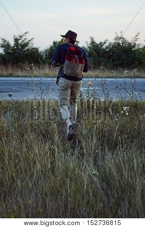 Adventurous man wearing hat and backpack strolling around the country road field