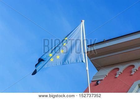 EU flag in front of an old building in the background a blue sky