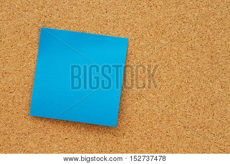 Bulletin board with a blank blue sticky note with copy space for your message
