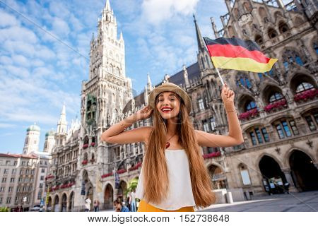 Portrait of a young female tourist with german flag standing on the central square in front of the town hall building in Munich. Having a great vacation in Germany