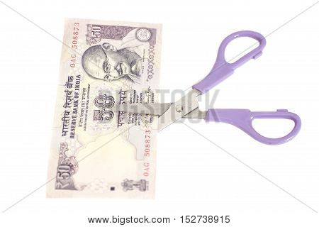 Fifty Rupee banknotes with scissors (Indian currency) isolated