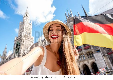 Young female tourist making selfie photo with german flag on the central square in front of the town hall building in Munich. Having a great vacation in Germany