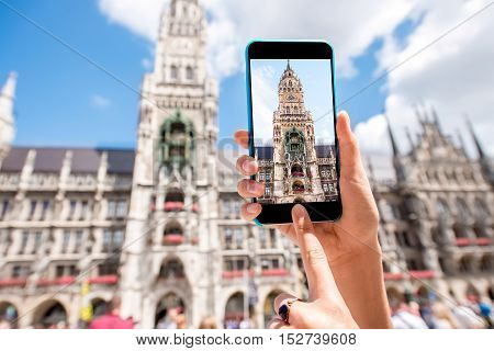 Photographing with smart phone the clock tower of the town hall in Munich city, Germany