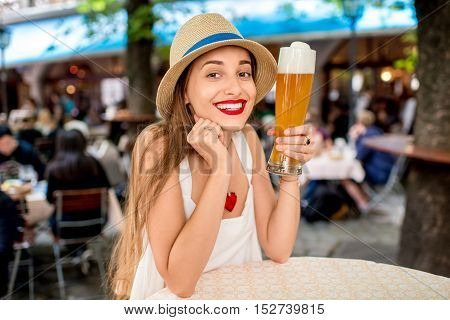 Young female tourist sitting with beer outdoors at the pub in Munich, Germany. Woman drinking a beer in Bavaria
