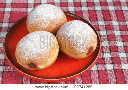 German doughnuts filled with jam in plate on red tablecloth
