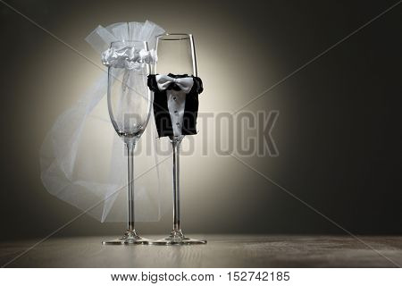 Two empty wineglass dressed in veil and wedding tuxedo