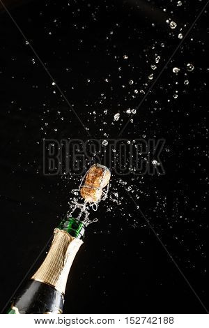 Closeup of champagne explosion. Vertical image on black background