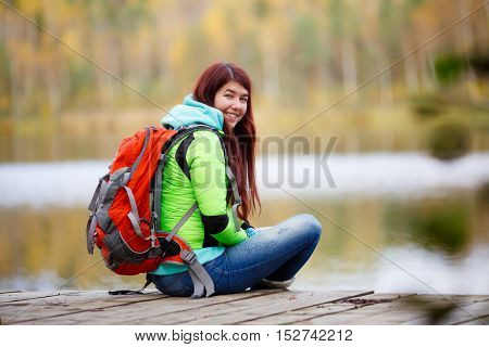 Cheerful brunette sitting with backpack at lake