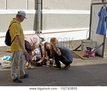 MOSCOW, RUSSIA - July 31, 2016: Squatting young adult girl and guy examine lying on the ground an open suitcase next to the bent over them by the seller senior adult woman at the flea market. July 31, 2016 in Moscow, Russia