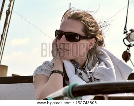 Cute woman deep in thought by sailing