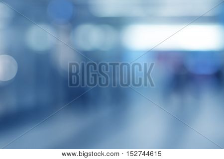blue blurred background of lobby or corridor with silhouettes of people