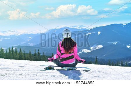 The young beautiful woman in mountains has a rest in the winter at the weekend meditation yoga