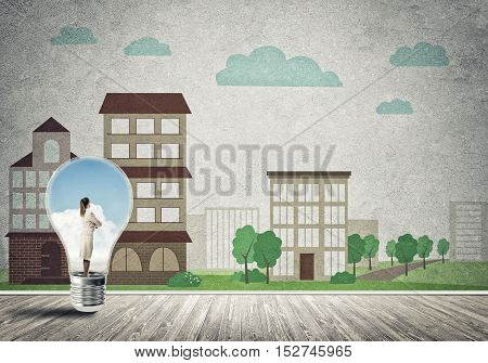 Businesswoman inside light bulb against city drawn concept