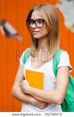 Thoughtful girl with glasses on background of Orange fence